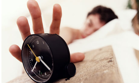 Young man in bed waking up and reaching for alarm clock